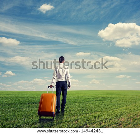 back view of businessman with bag walking through the green field