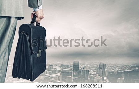 Back view of businessman with suitcase looking at city - stock photo