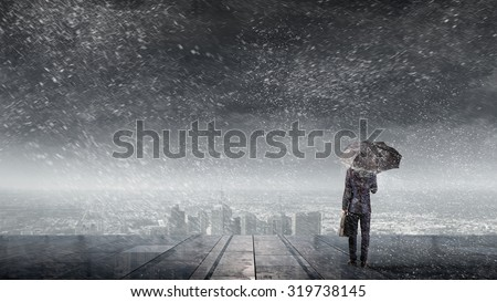 Back view of businessman with umbrella looking at city