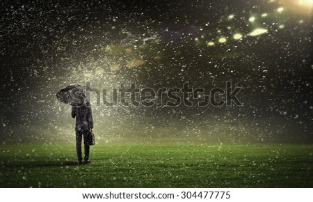 Back view of businessman with umbrella standing under rain - stock photo