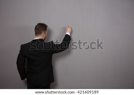 Back view of businessman writing something on wall in studio. Young man in black suit explaining some diagrams or projects. - stock photo