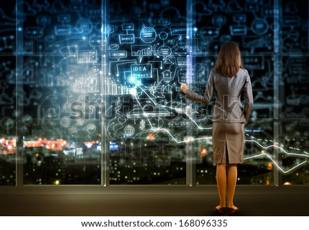 Back view of businesswoman drawing business plan - stock photo