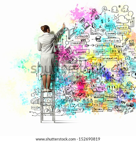 Back view of businesswoman drawing colorful business ideas on wall - stock photo