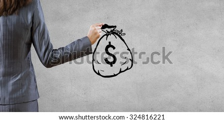 Back view of businesswoman holding drawn money bag