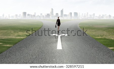 Back view of businesswoman standing on crossroads and making choice