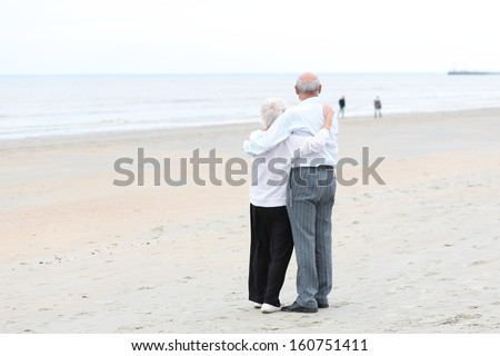 Back view of caring couple of two seniors, a man and his wife, standing together on a sandy peaceful beach looking at the ocean  - stock photo