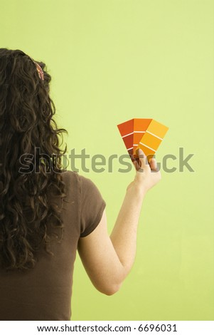Back view of Caucasian brunette woman holding paint color swatches.