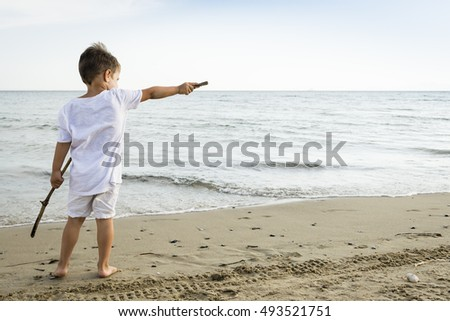 Back view of caucasian child in white dressing having fun pointing something on the beach