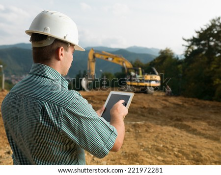back view of caucasian engineer standing on construction site checking plan on digital tablet - stock photo