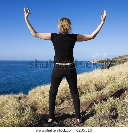 Back view of Caucasian mid-adult woman standing on Maui, Hawaii coast with arms raised above head. - stock photo