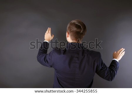 Back view of Caucasian young man in a navy blue suit pointing on dark grey background - stock photo
