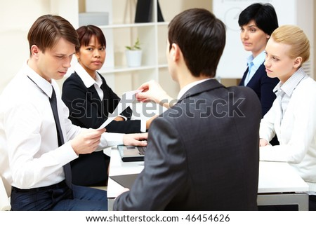 Back view of chief passing over paper to employee while the others looking at them - stock photo
