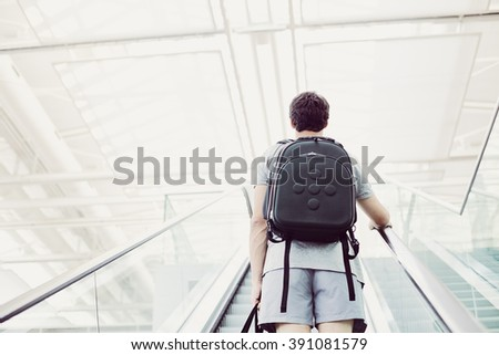 Back view of college student with backpack going up airport escalator holding travel bag in his hand - journey concept - stock photo