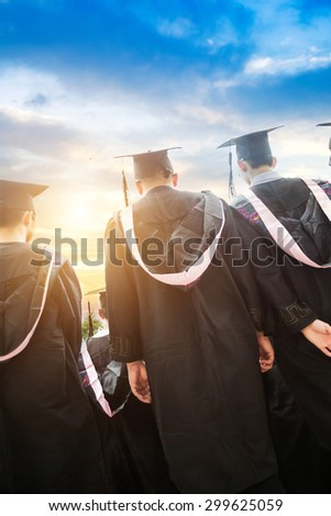 back view of college students with cap and gown celebrate graduation - stock photo