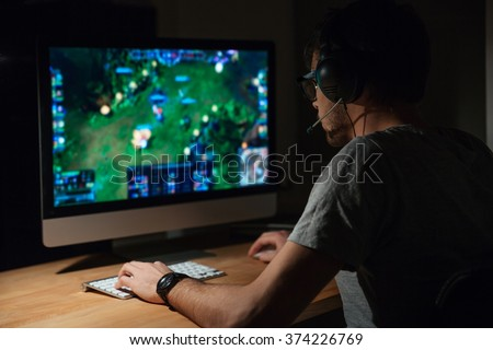 Back view of concentrated young gamer in headphones and glasses using computer for playing game at home