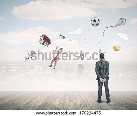 Back view of confident businessman looking at city with items flying in air