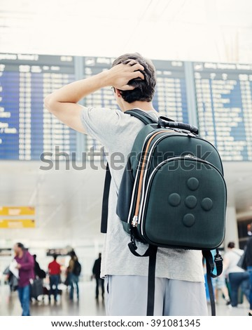 Back view of confused college student traveling with backpack, standing with hand on his head and checking information about his flight on airport timetable - travel concept - stock photo
