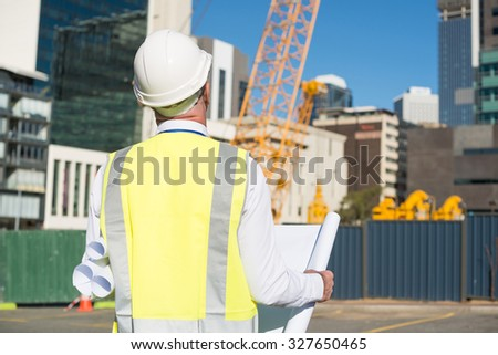 Back view of construction engineer in hardhat looking at building - stock photo