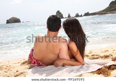 Back view of couple looking at the sea - stock photo