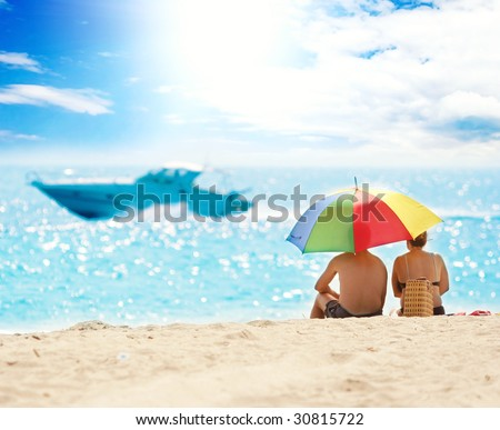Back view of couple on beach looking at the sea - stock photo