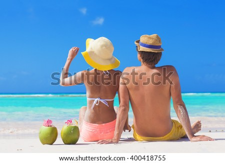 back view of couple sitting on tropical beach with two fresh coconut cocktails - stock photo