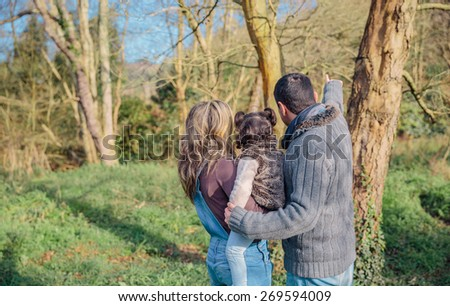 Back view of couple with her little daughter enjoying together of the forest landscape. Family leisure time concept. - stock photo