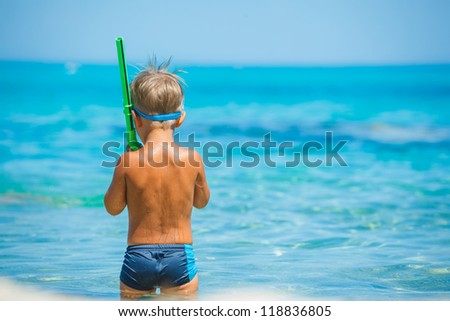 Back view of cute boy snorkelling ready swimming in the transparent sea - stock photo