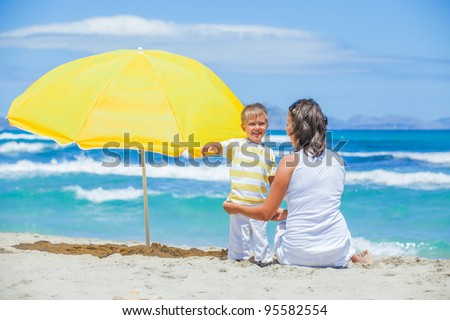 Back view of cute 2 years old boy and his mother with big umbrella on tropical beach