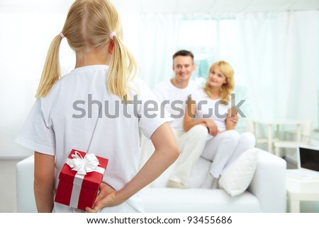 Back view of daughter hiding giftbox while looking at her parents