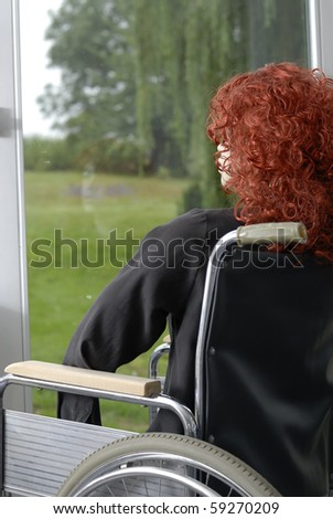 Back view of disabled woman in wheelchair looking at the garden - stock photo