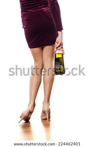 back view of drunk woman with a bottle in her hand - stock photo