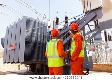 back view of electricians standing next to a transformer in electrical power plant - stock photo