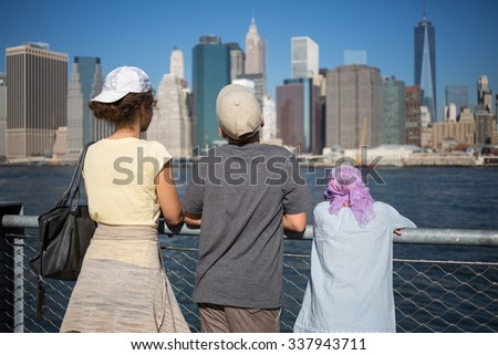 Back view of family of three are standing on the quay at autumn day. - stock photo