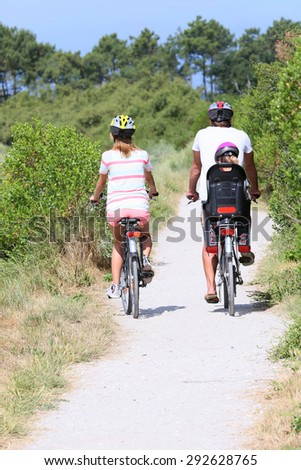 Back view of family riding bikes on a summer day - stock photo