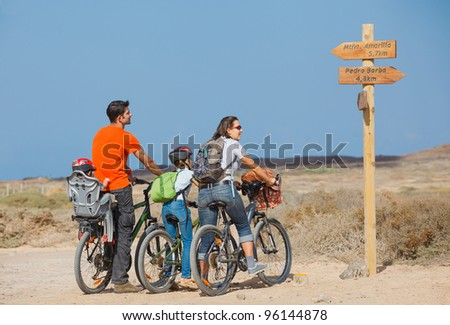 Back view of family with baby and girl child having a weekend excursion on their bikes on a summer day in beautiful landscape - stock photo