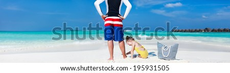 Back view of father and daughter at tropical beach. Wide panorama, perfect for banners - stock photo