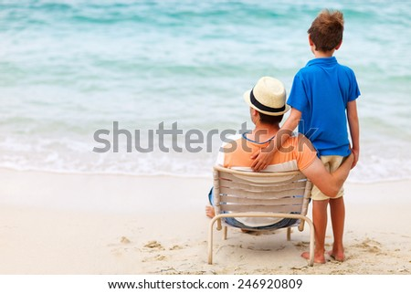 Back view of father and son at beach - stock photo