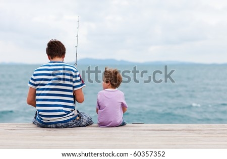 Back view of father and son fishing together from jetty - stock photo