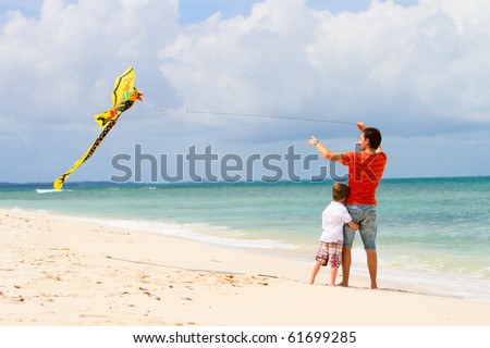 Back view of father and son flying kite at beach