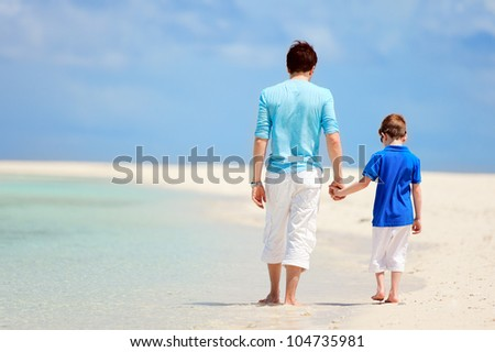 Back view of father and son walking at tropical beach - stock photo