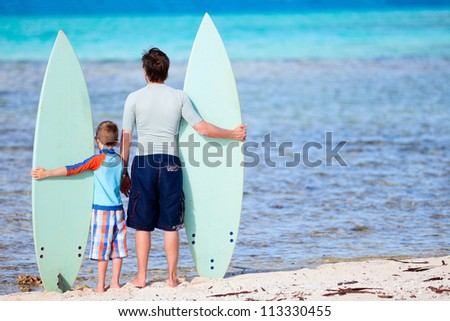 Back view of father and son with surfboards at beach - stock photo