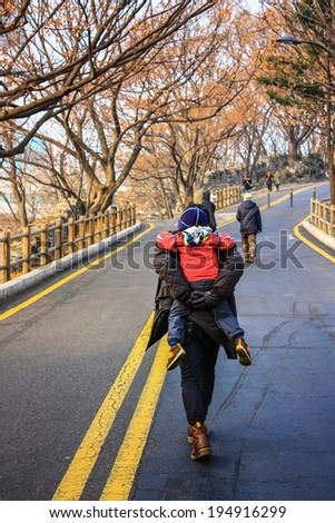 Back view of father carrying his son on the road in winter - stock photo