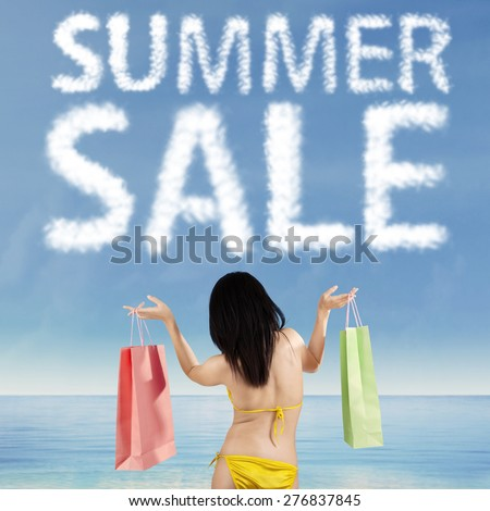 Back view of female shopaholic wearing swimsuit on the shore while holding two shopping bags under cloud shaped a summer sale text - stock photo