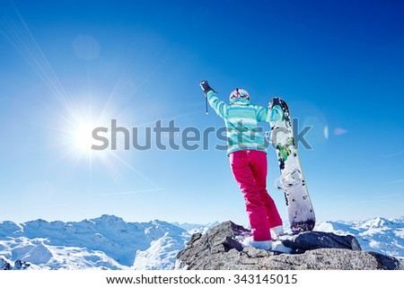Back view of female snowboarder wearing blue jacket, gloves and pink pants standing with snowboard in right hand and raising left arm against sunny alpine mountain landscape - winter sports concept - stock photo