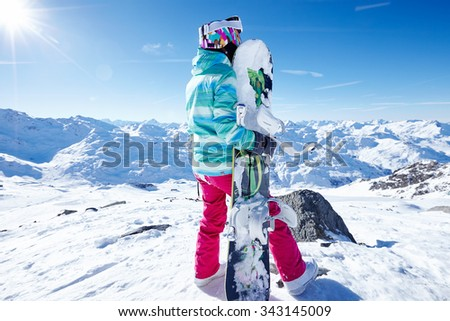 Back view of female snowboarder wearing colorful helmet, blue jacket, grey gloves and pink pants standing with snowboard in hand and enjoying sunny alpine mountain landscape - winter sports concept - stock photo