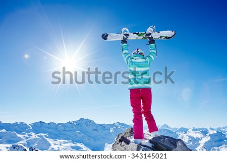 Back view of female snowboarder wearing colorful helmet, blue jacket, grey gloves and pink pants standing with snowboard raised overhead and enjoying sunnymountain landscape - winter sports concept - stock photo