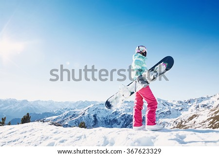 Back view of female snowboarder wearing colorful helmet, blue jacket, grey gloves and pink pants standing with snowboard in one hand and enjoying alpine mountain landscape - snowboarding concept - stock photo