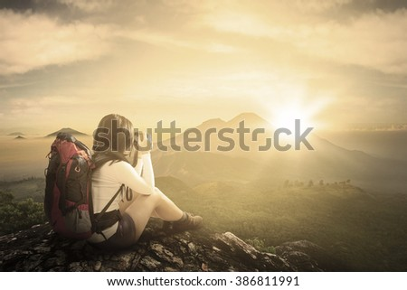 Back view of female traveler sitting on the rock while taking pictures with digital camera on the mountain - stock photo