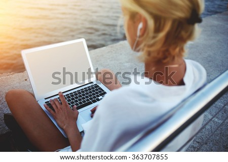 Back view of female using net-book with blank copy space screen for your text message or promotional content, young woman reading news via laptop computer while sitting near sea during her vacations - stock photo