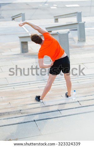 Back view of fit men stretches muscles before morning jog outdoors in summer day, young sportsmen dressed in sportswear workout in the fresh air, male runner engaged in physical exercises outdoors - stock photo